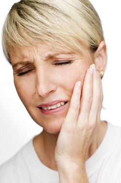 Woman with short blond hair wincing and holding jaw in pain