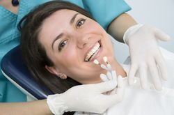 Hygienist holding shade samples up to smiling female patient's teeth