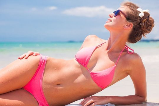 Slim woman in a pink bikini lying on the beach