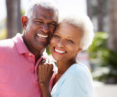 An older couple smiling together outdoors