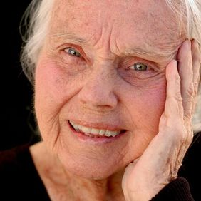 An elderly woman with her hand resting against her face