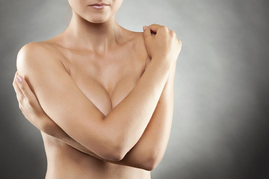 A breast reconstruction patient with her arms folded in front of her body