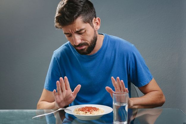 A man in a blue shirt avoiding food.