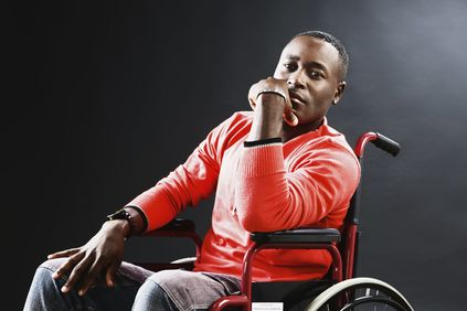 Man wearing an orange sweater in wheelchair.