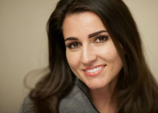 Dark-haired woman with a white smile
