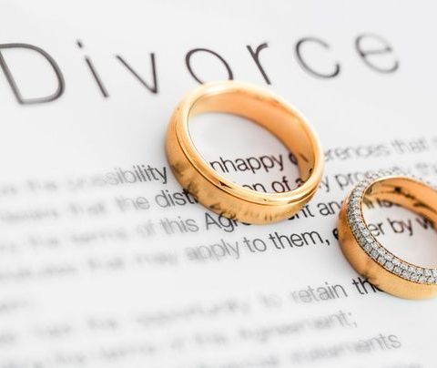 Photo of rings on top of a divorce agreement