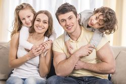 Smiling couple with young boy and girl hugging them on a couch