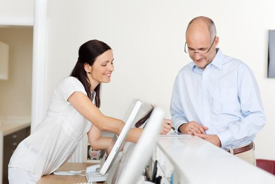 A receptionist reviewing paperwork with a patient