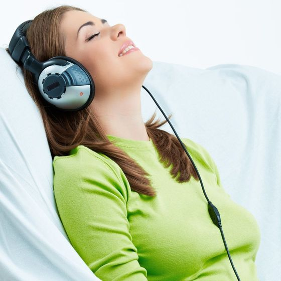 Woman looking relaxed while listening to music through headphones