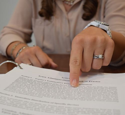 Woman's hand pointing to legal paperwork
