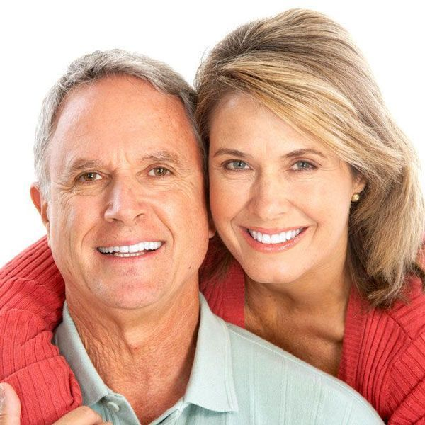 couple smiling after experiencing relief from a mouth guard