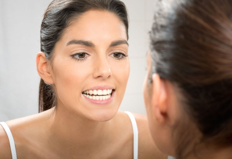 Woman looking at teeth in the mirror