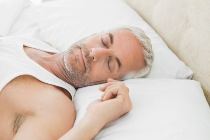 Man in white shirt sleeping peacefully against white pillows