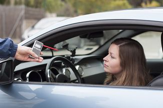 a police officer holding a breathalyzer for a woman in a car