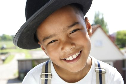 Young boy in hat smiling.