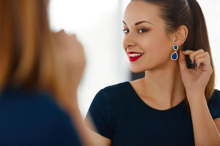 Attractive woman holding earring to ear