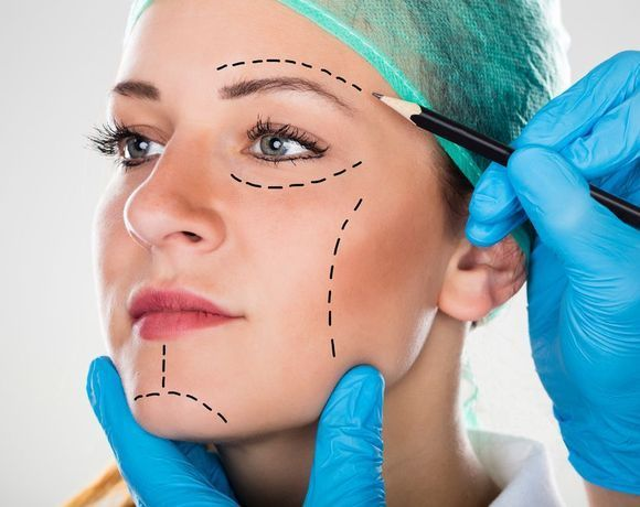 Surgeon drawing lines on beautiful woman's face