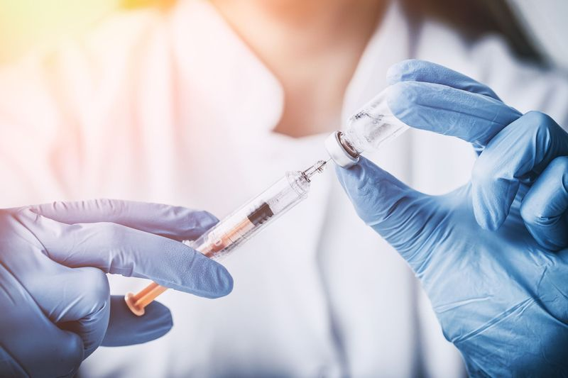Medical practitioner drawing medication from bottle into syringe