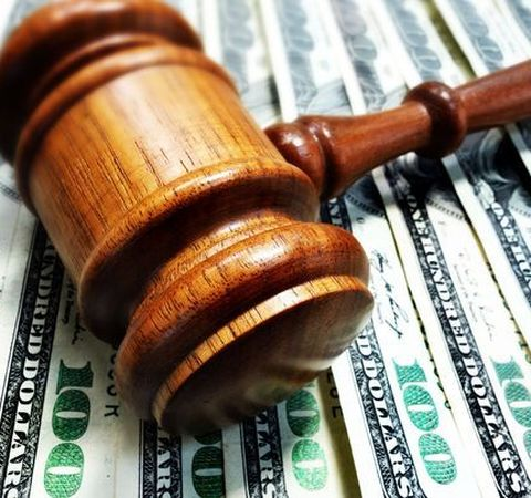 Photo of a gavel on top of money