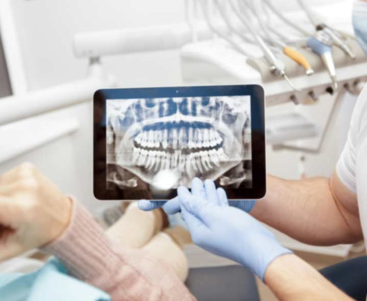 Dentist showing patient x-ray on iPad