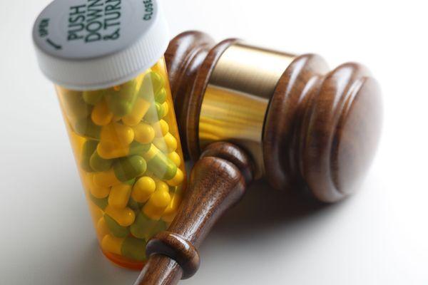A closeup shot of a prescription bottle and a gavel.