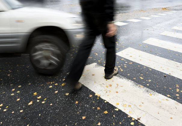 Photo of a pedestrian in a crosswalk with a moving vehicle