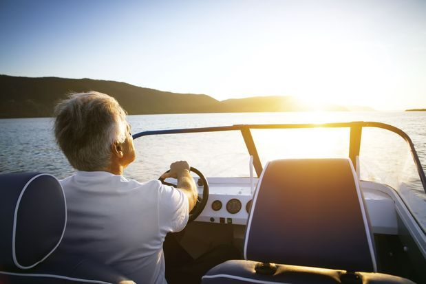 Older man driving a boat.