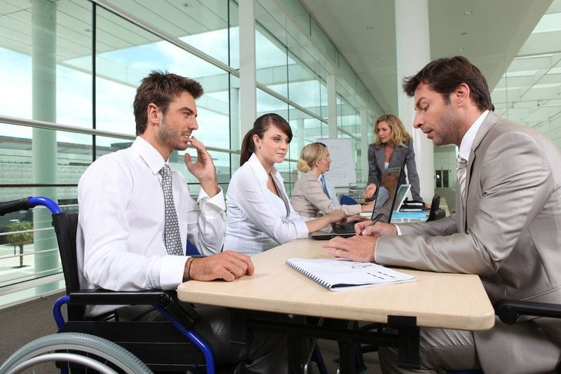 A man in a wheelchair sits at a conference table with other coworkers.
