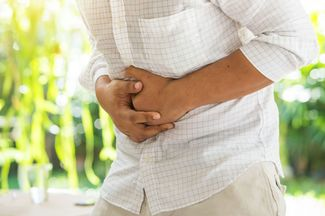Man holding on stomach in discomfort