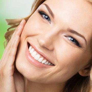 Attractive smiling woman with white, straight teeth holding hand to cheek