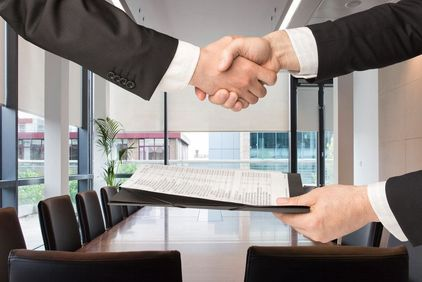 Business men shaking hands and exchanging paperwork