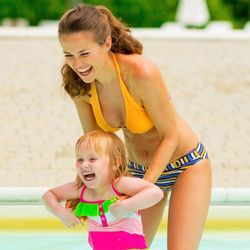 Photo of smiling woman and child in swimsuits