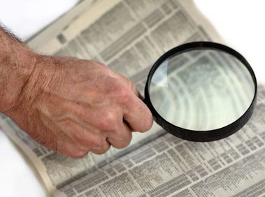 Elderly reader using strong magnifying glass to view phone book