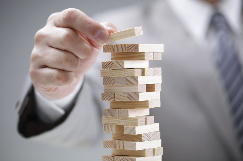 Photo of a man in a business suit playing jenga