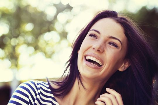 Dark-haired woman smiling outdoors