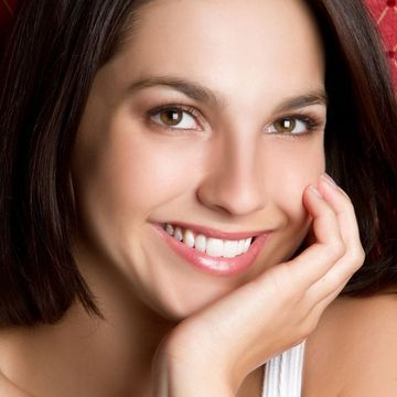 Attractive brunette smiling with chin in hand