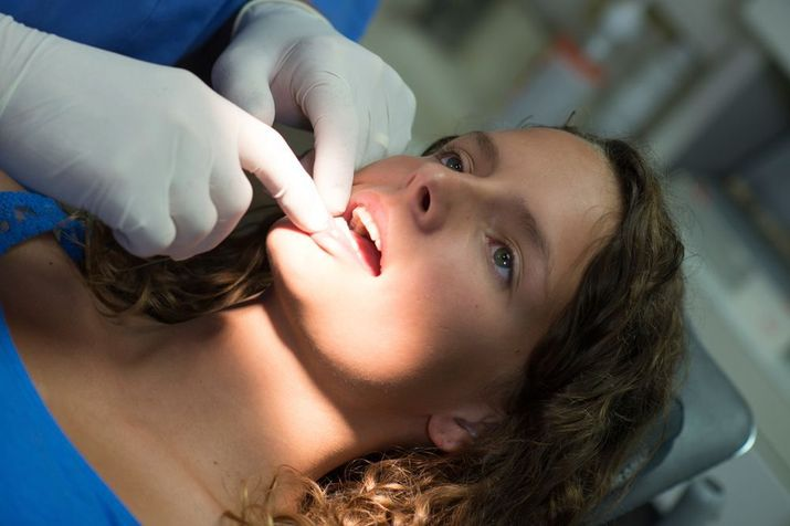Female patient undergoing oral cancer screening.