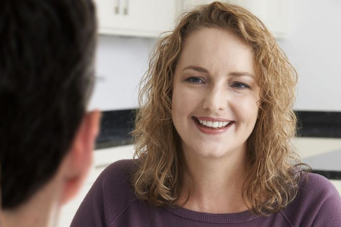 Smiling woman talking to doctor