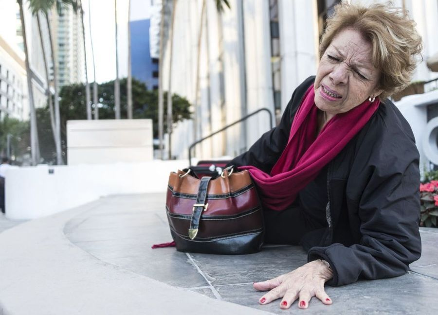 An older woman lies on the ground outside an office building