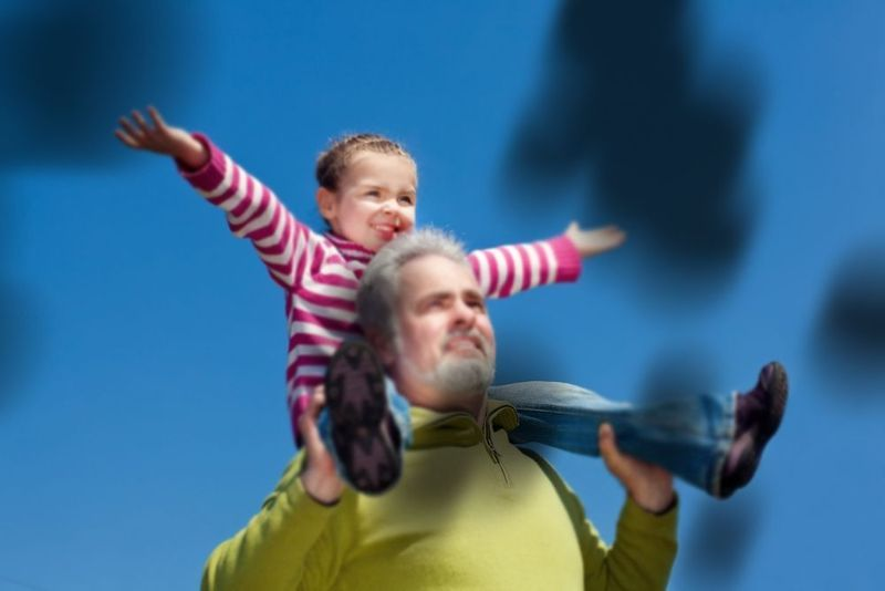 A photo of an older man carrying a child on his shoulders, blurred and blacked out in places.