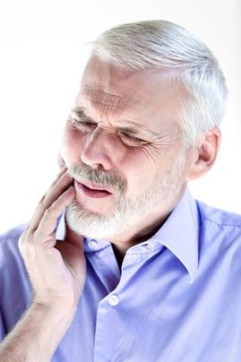 An older man experiencing tooth pain