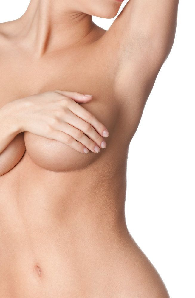A beautiful, Caucasian woman with large breasts holds one arm up while her other arm covers her naked breasts.