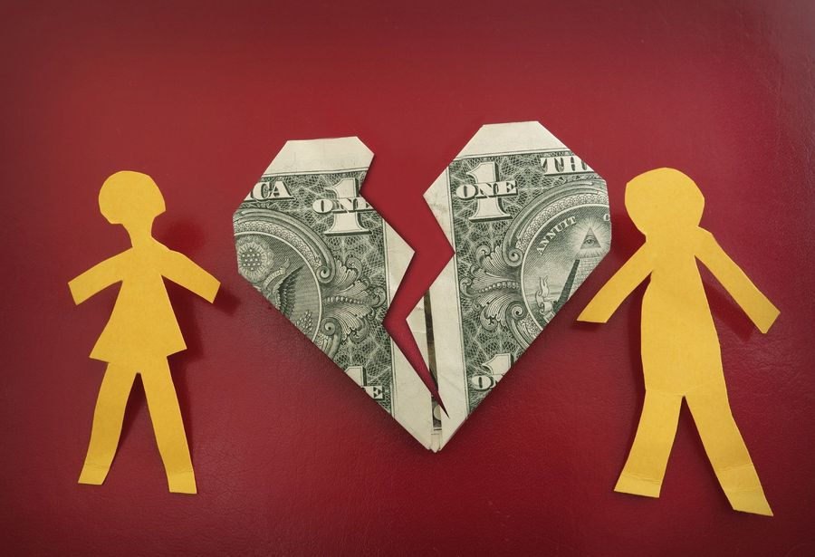 Two yellow paper figures separated by a broken heart fashioned from a folded dollar bill