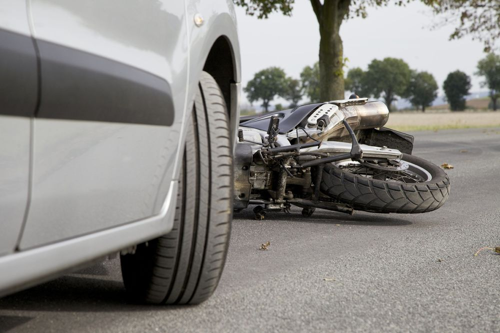 A motorcycle lies on the ground under an automobile
