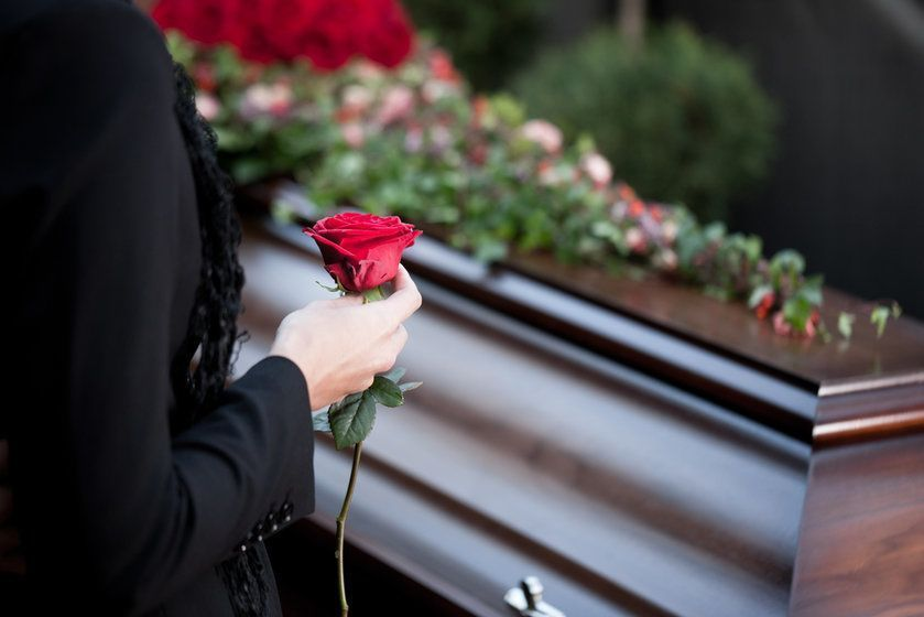 A woman holds a rose in front of a casket