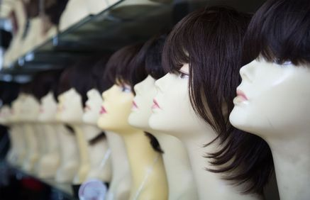 Row of wigs on mannequin heads