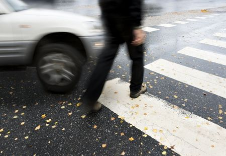 Photo of a person in a crosswalk and a car