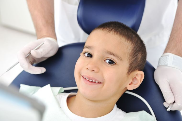 A young boy sits in the dentist's chair.