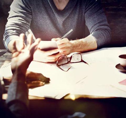 Men talking over paperwork