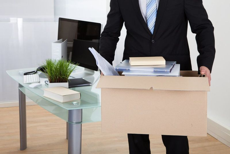A man in a suit carries a box of personal belongings away from his desk.